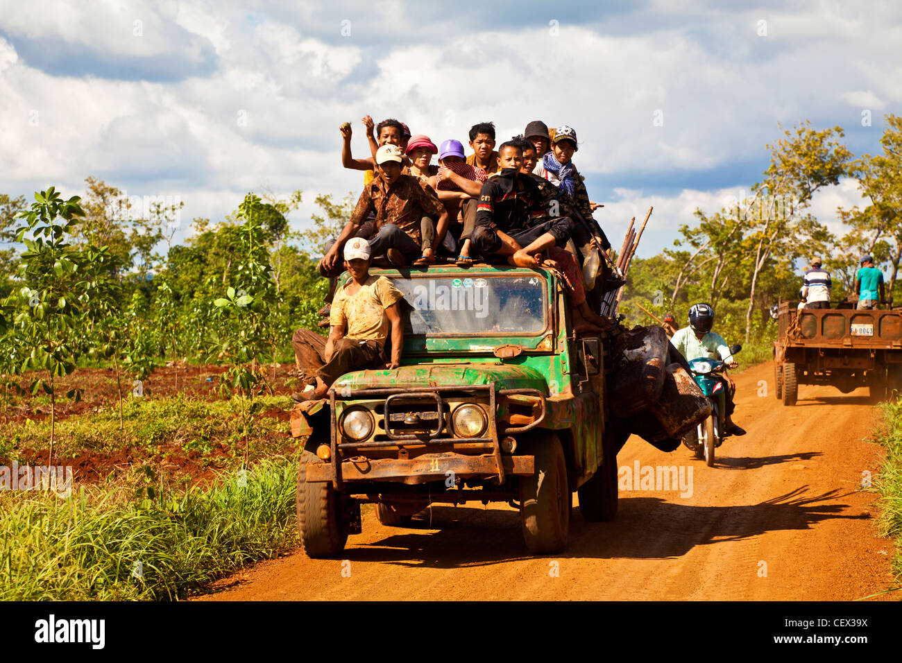 People crowded onto a truck on a dust track in a village near Banlung, Cambodia - Stock Image