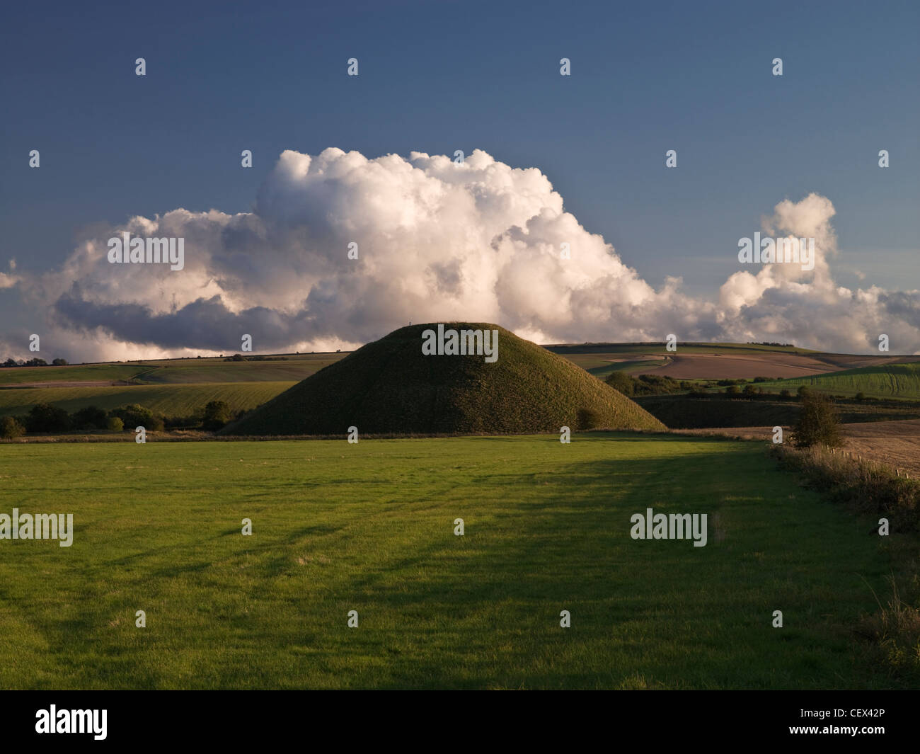 View of Silbury Hill, the tallest prehistoric human-made mound in Europe, against a bank of cloud on a clear evening. - Stock Image