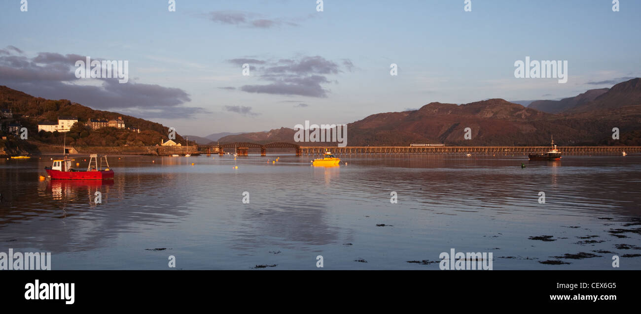 Barmouth harbour and railway bridge - a train is crossing the bridge. - Stock Image