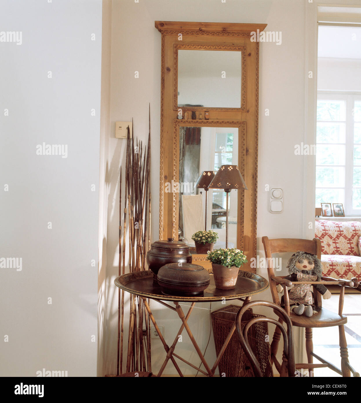 REAL HOMESDetail of hallway, with wood framed mirror, small table and chair, high chair, small lamp and decorative - Stock Image
