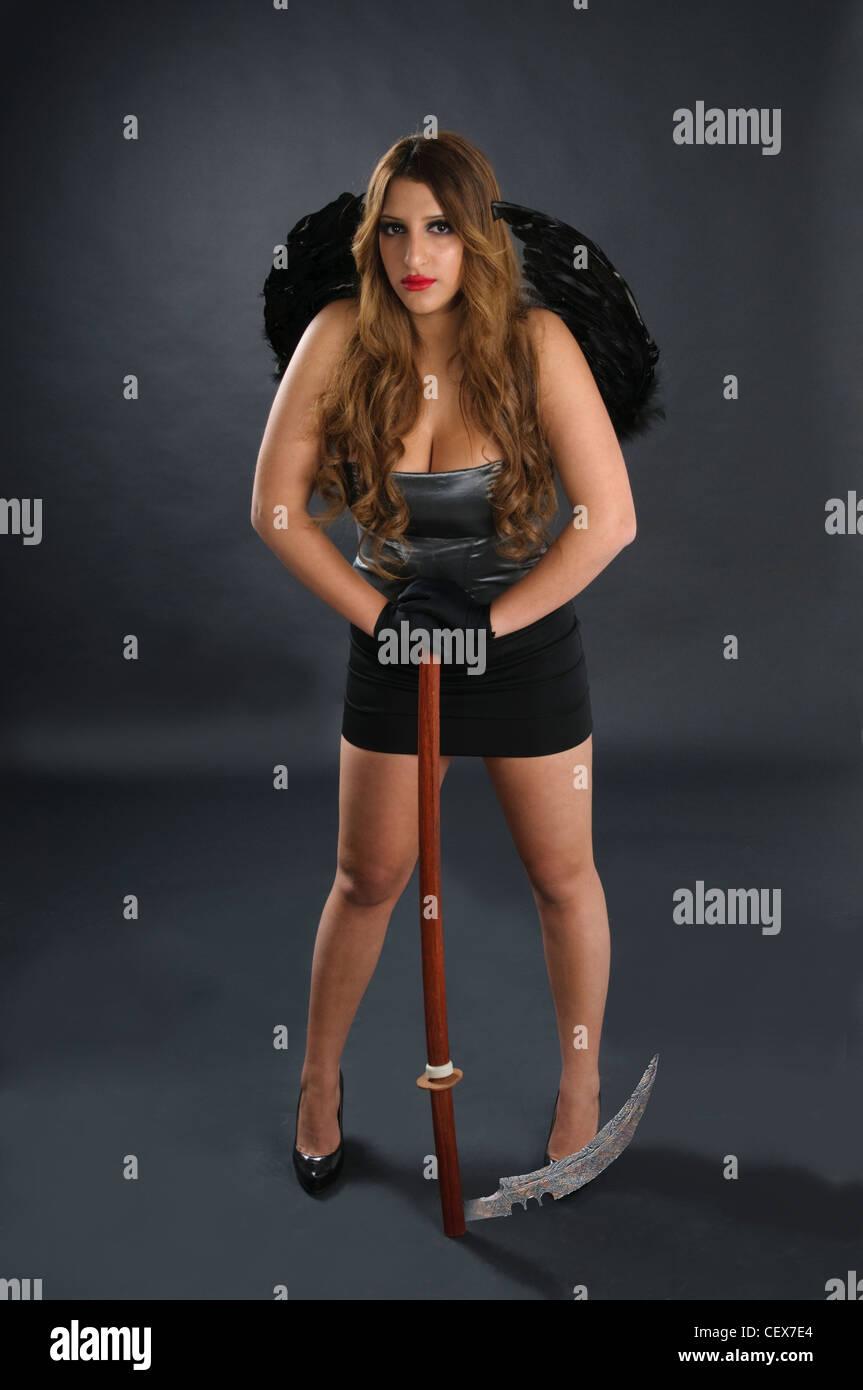Grim reaper female DEATH carrying scythe - Stock Image