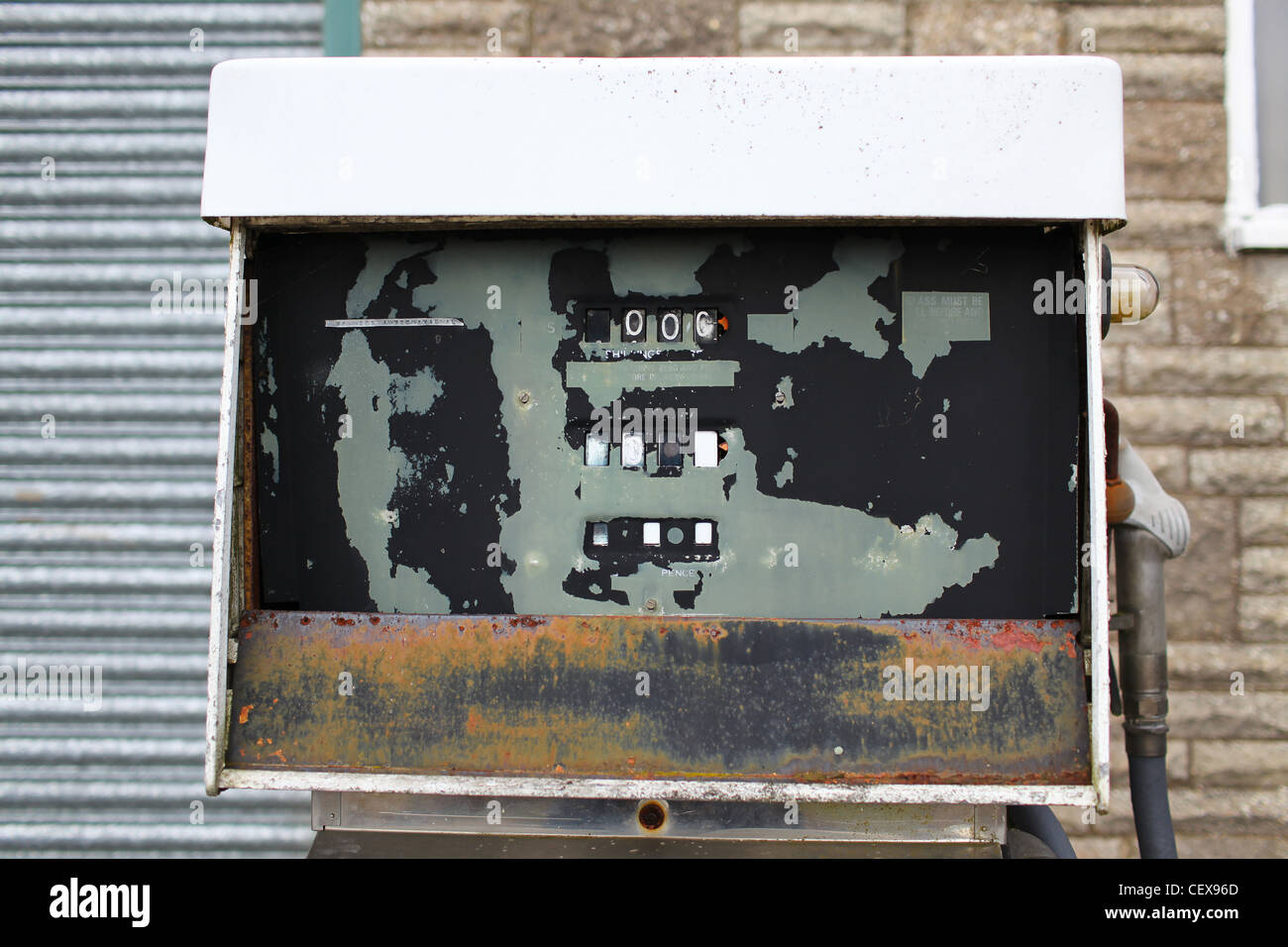 Antique unused broken petrol pump outside a garage door - Stock Image