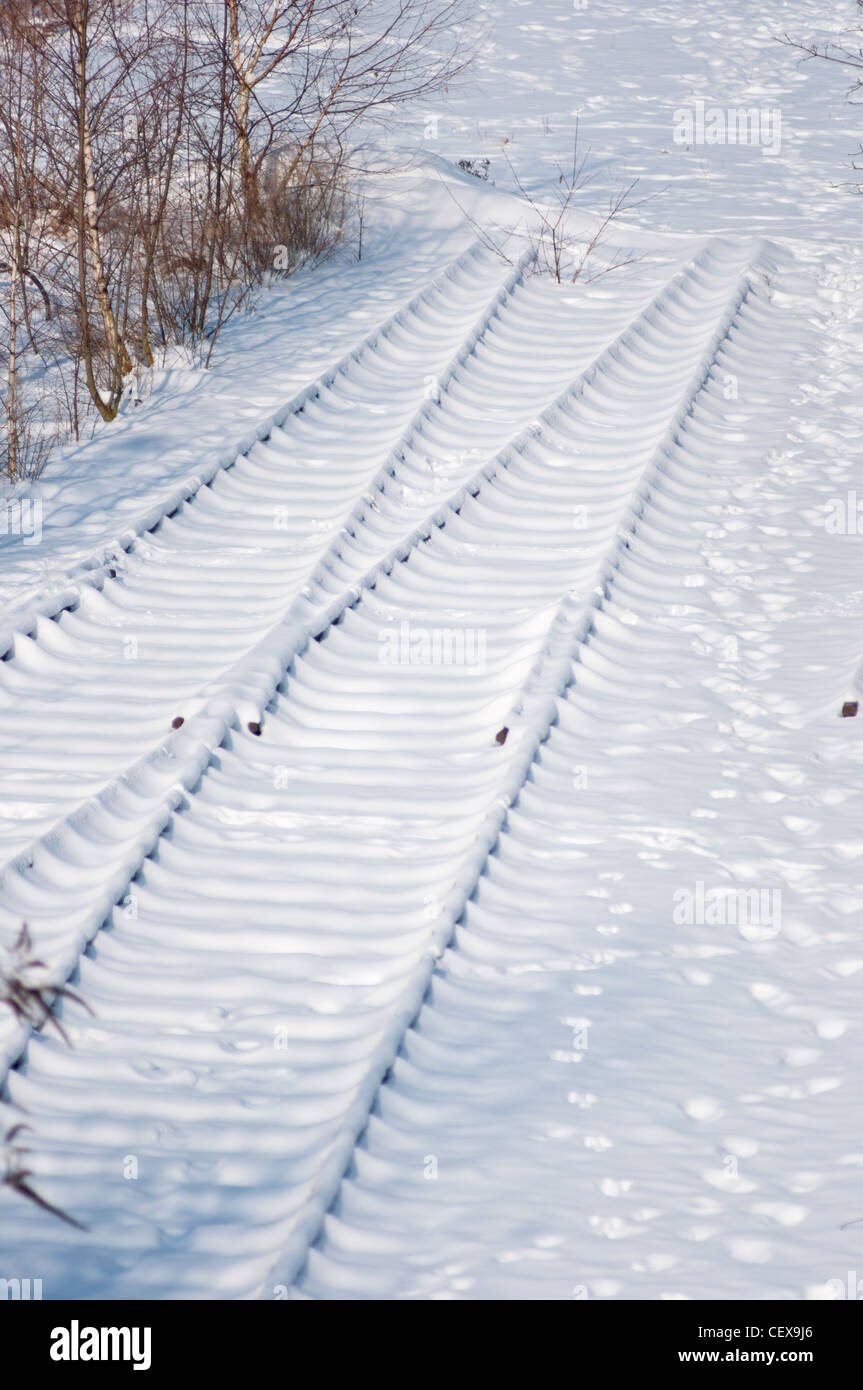 End of the line - Disused rail tracks covered in snow in Munich, Germany. - Stock Image