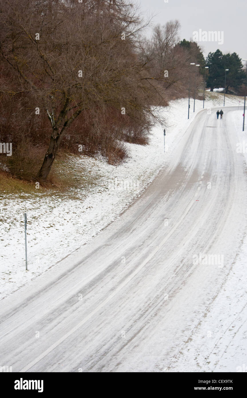 A treacherous looking road covered with snow through Olympic park, Munich, Germany. - Stock Image