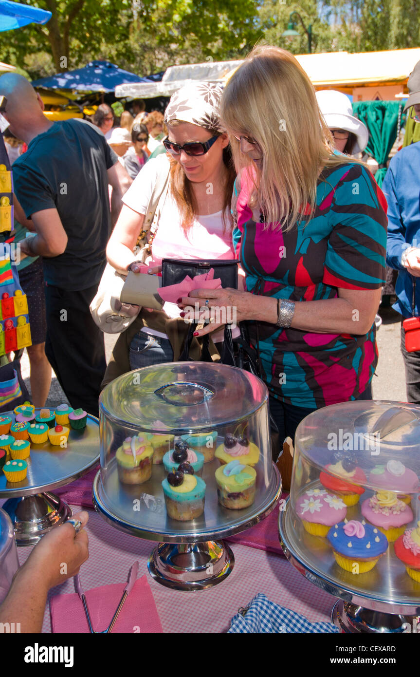Mother and daughter shopping at market in christucurch square, Canterbury market cake stall - Stock Image