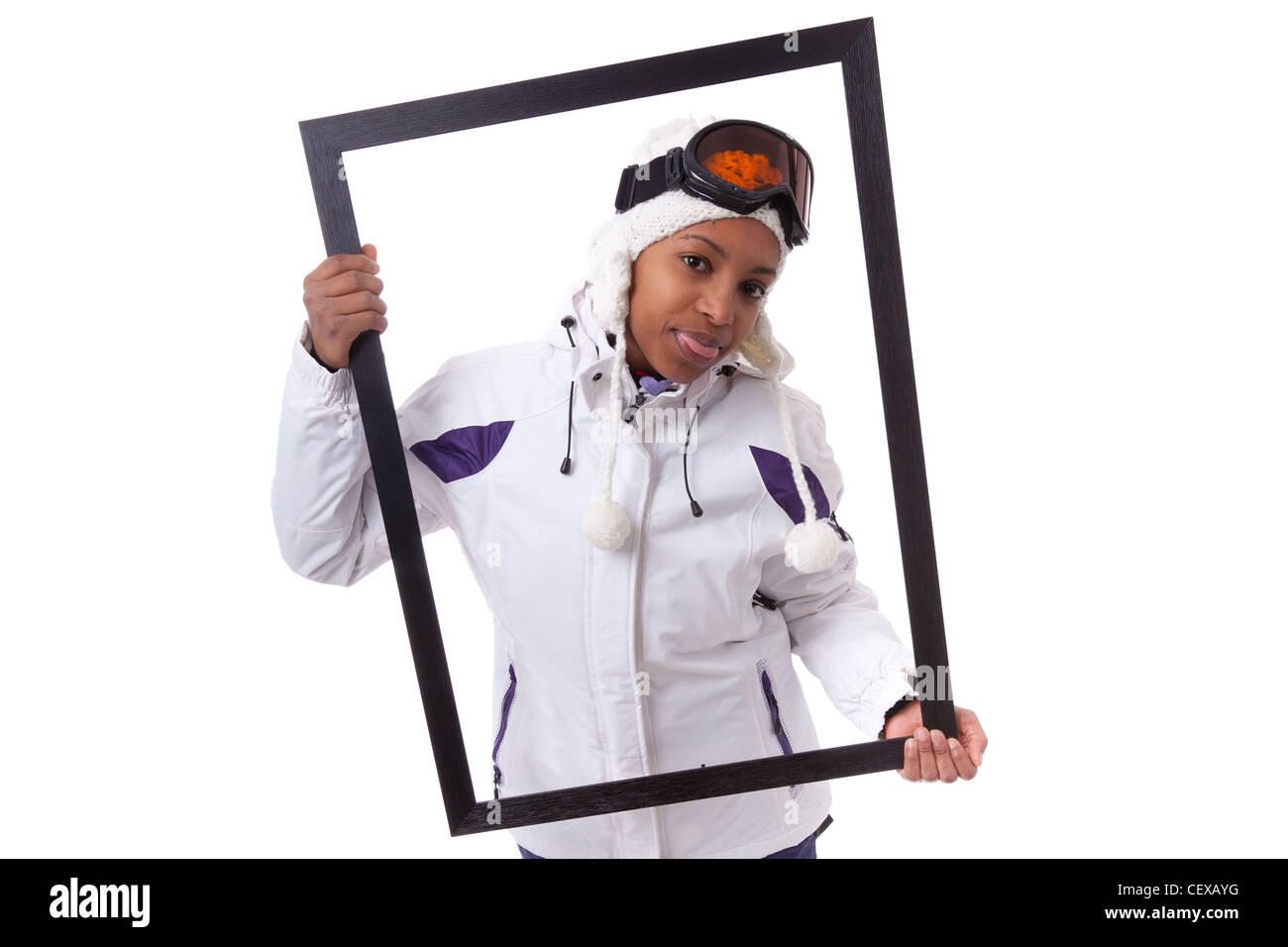 Young african woman in ski clothes holding a picture frame, isolated on white background - Stock Image