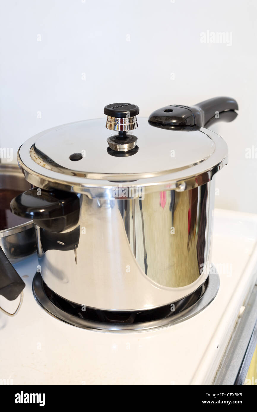 A pressure cooker/ pot on a stove. - Stock Image