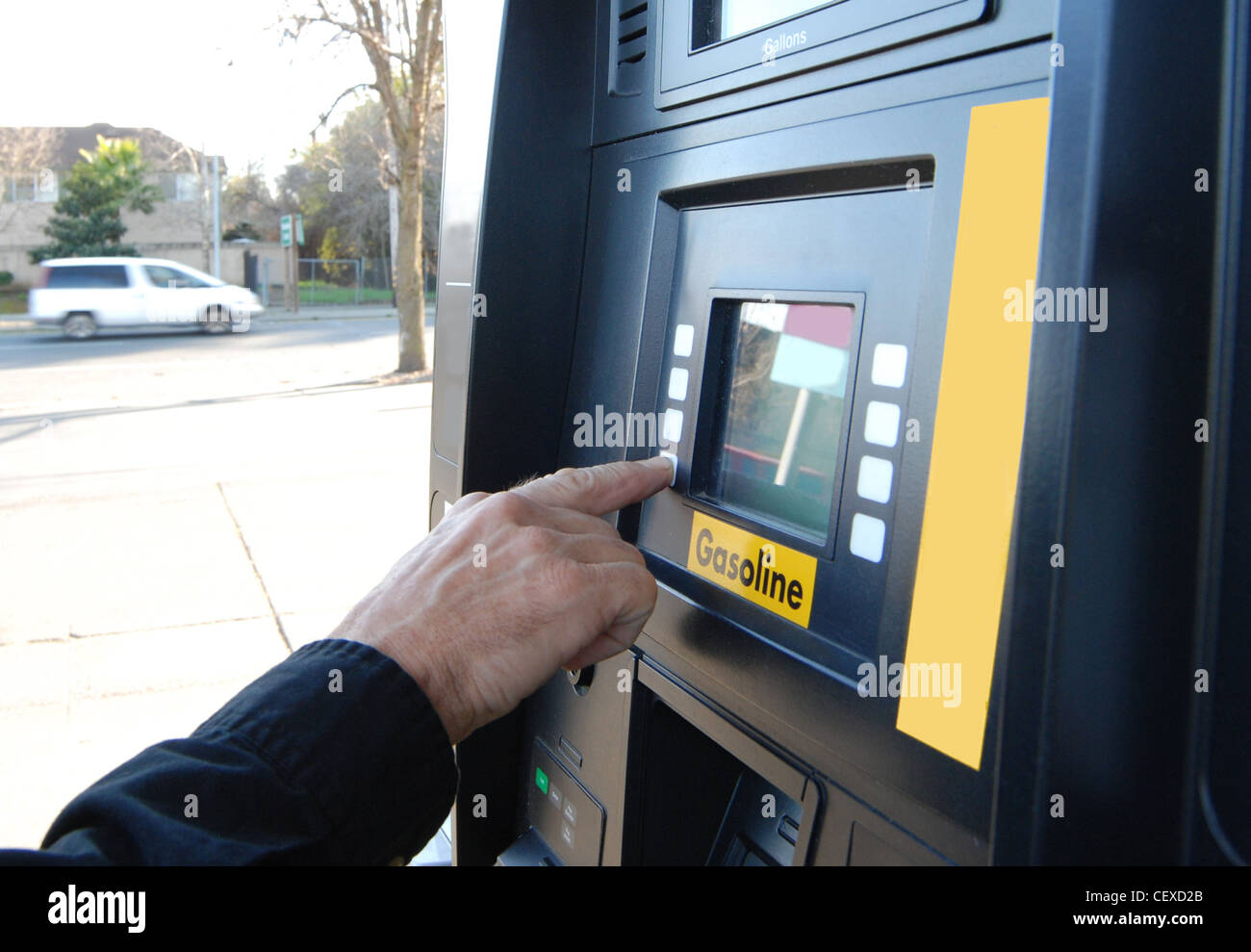 Close up of customer's hand pushing buttons on a gasoline fuel pump - Stock Image