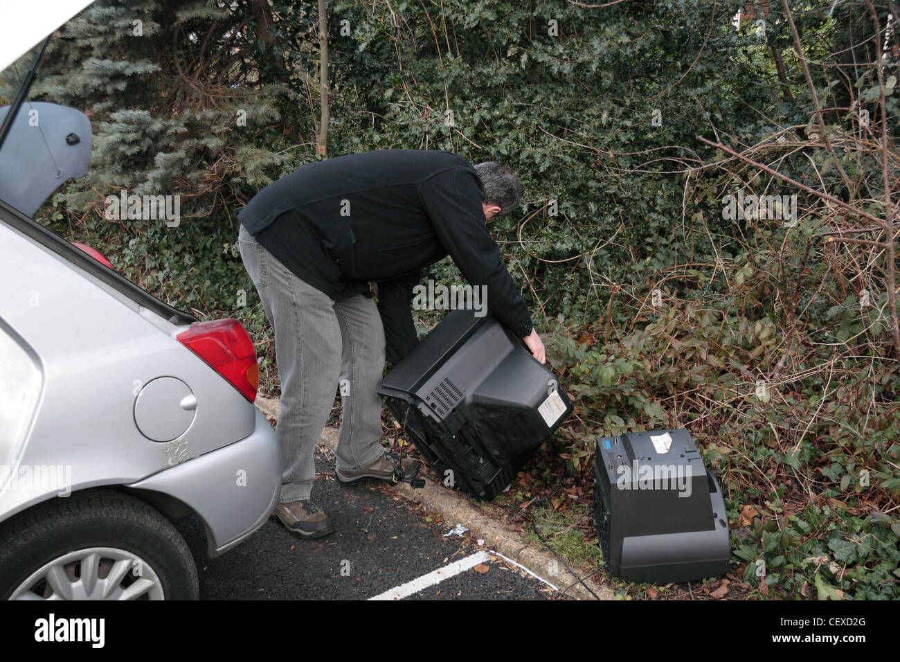 A man illegally dumping (fly tipping) some large items including televisions on the side of a car park. ( Posed). - Stock Image