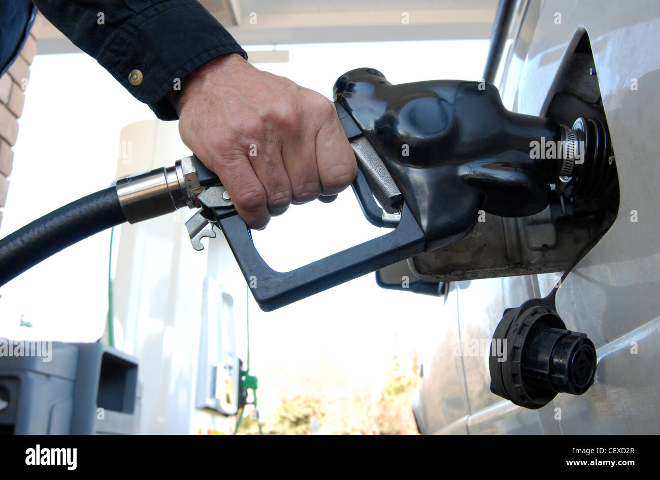Close up of a customer's hand pumping fuel into car's gas tank. - Stock Image