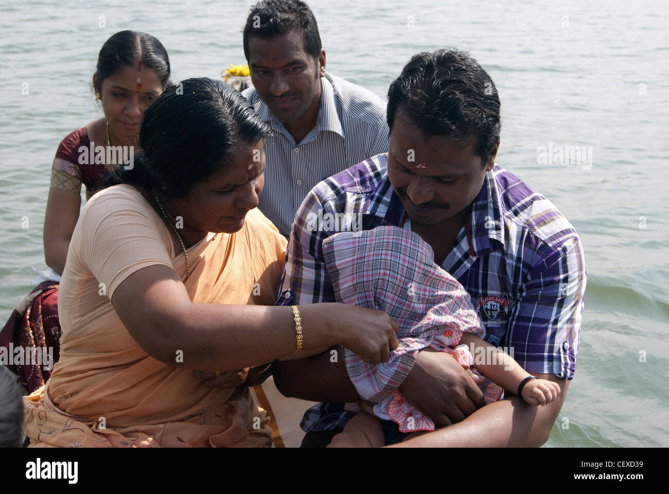 Funny scene from canoe Boat Journey through backwaters of Kerala.Baby head is covered with cloth for protecting - Stock Image