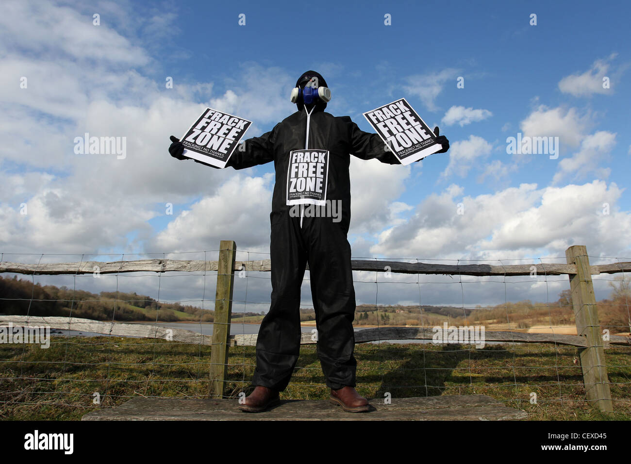 A masked man pictured protesting about the possibility of fracking taking place near Ardingly Reservoir, West Sussex, - Stock Image
