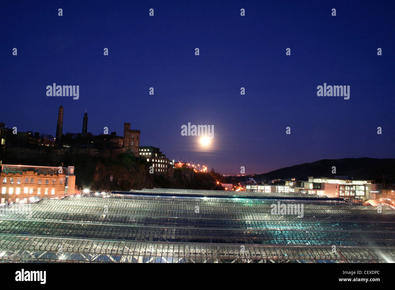 View over Edinburgh Waverley station from North Bridge skyline to Calton Hill large moon night sky dark blue backlit - Stock Image