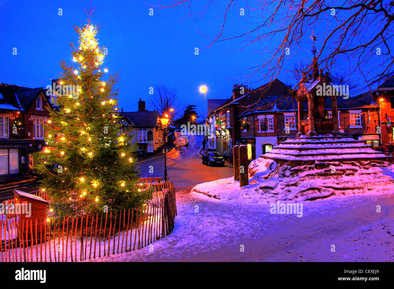 Xmas scene with snow at the Christmas Tree at Lymm Cross, Lymm village, Cheshire, England, UK - Stock Image