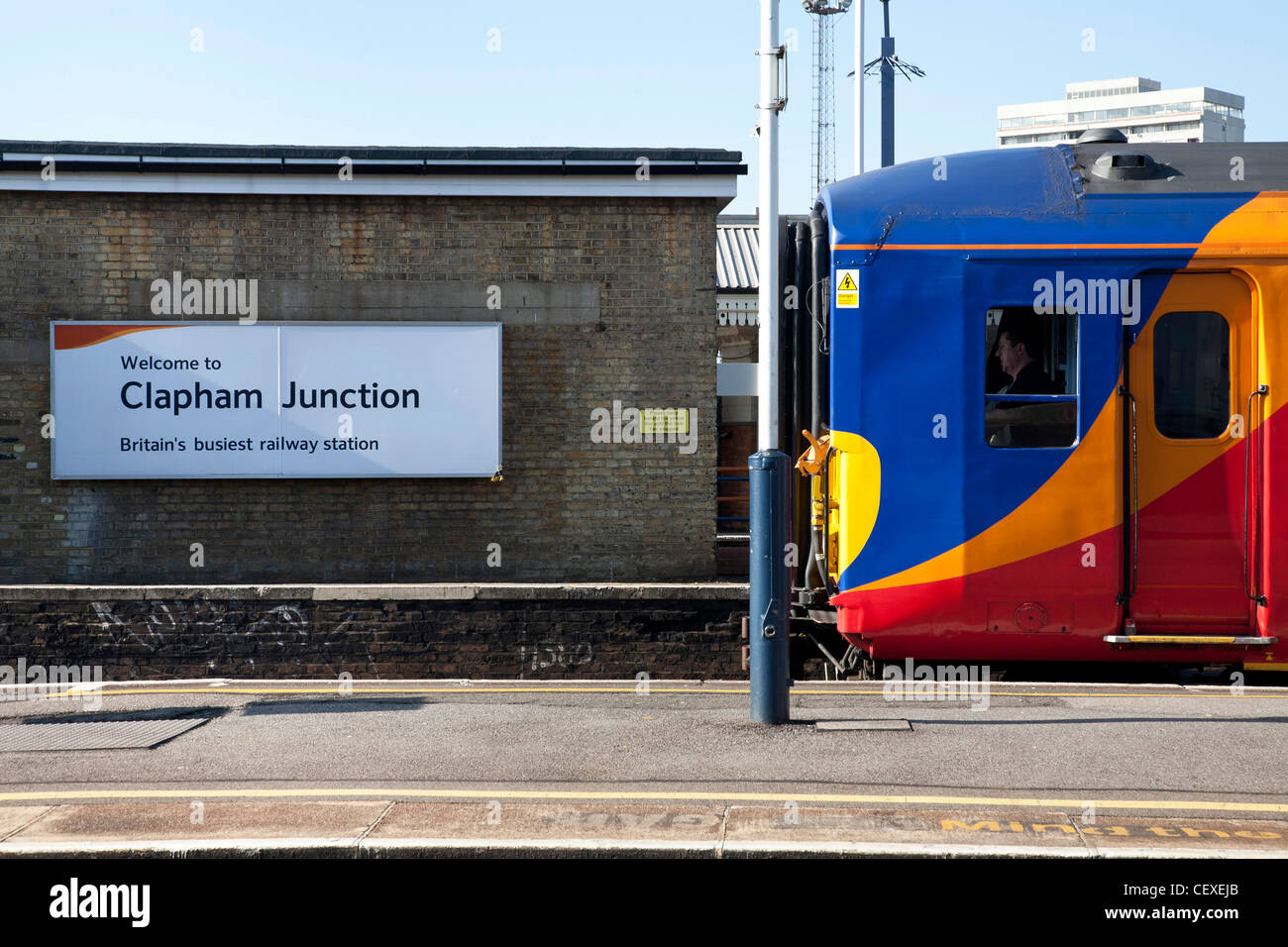 Welcome to Clapham Junction, Britain's busiest railway station. Sign and train at platform, driver in the cab. - Stock Image