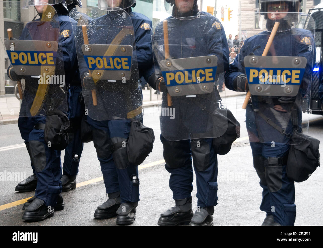 Riot police facing protesters on a downtown Toronto street during the G20 economic summit in the summer of 2010 - Stock Image