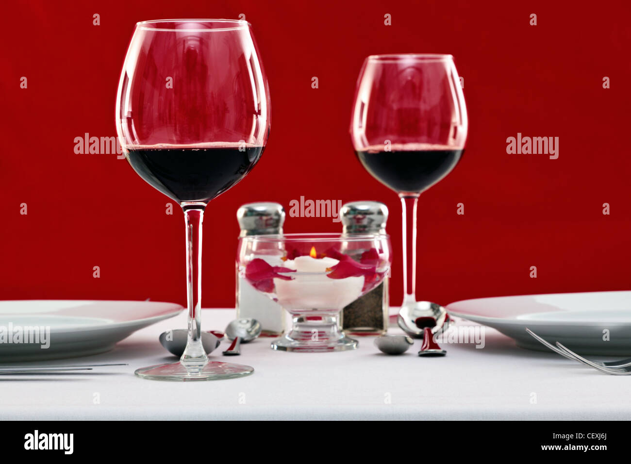 photo of a table setting with red wine glasses and a floating candle - Floating Wine Glass