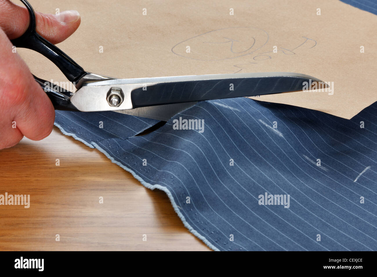 Photo of a piece of pinstripe material being cut around a bespoke template - Stock Image