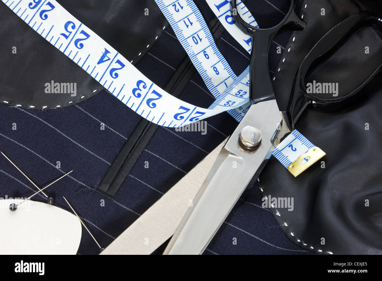 Still life photo of the inside of a bespoke suit jacket with hand stitching and scissors, tape measure, chalk and - Stock Image