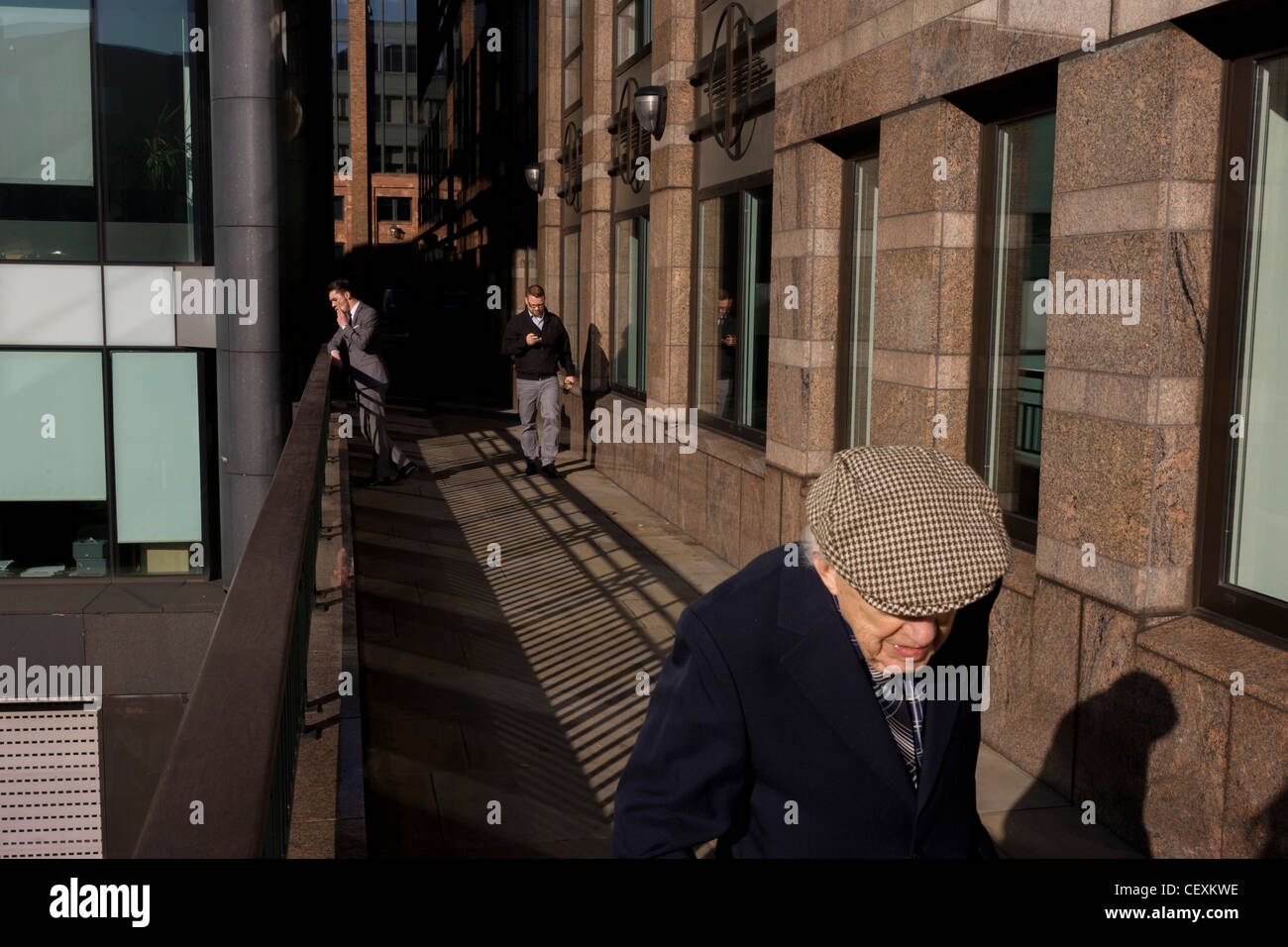 Elderly man walks along modern walkway, past a youthful office worker enjoying a thoughful moment in City of London. - Stock Image