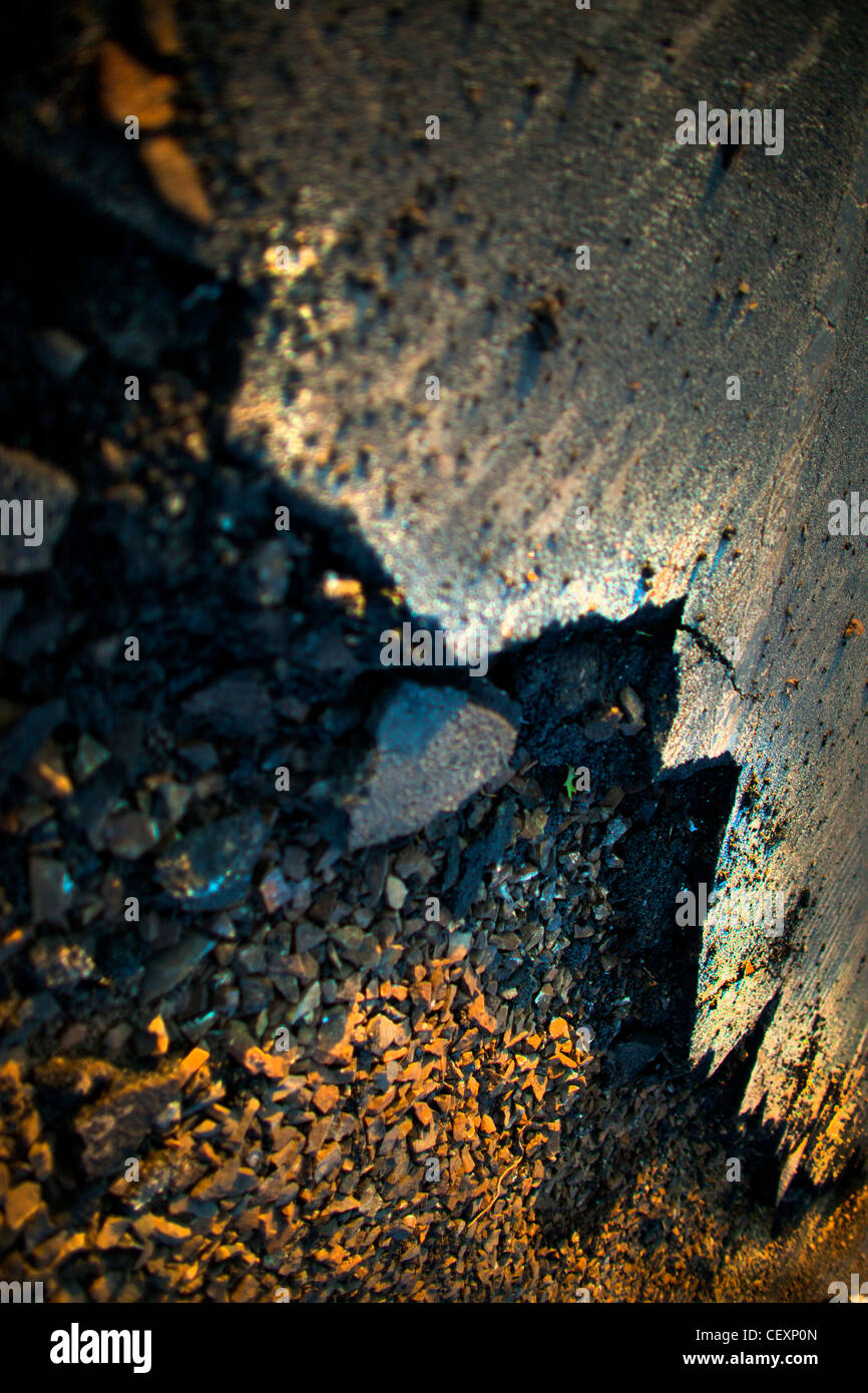 Pavement and road split, and crushed from force.  Overhead, vertical photo.  Could be from earthquake. Sharp, broken - Stock Image