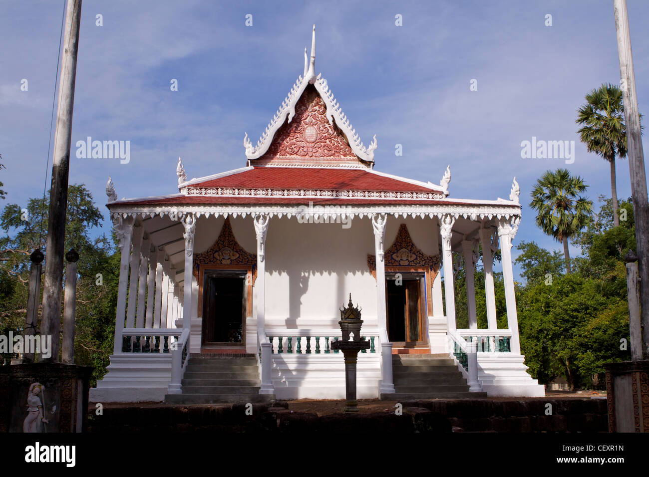 Original Wat Kampong Tralach 'Vihara' against a blue sky with palm trees, desecrated by the Khmer Rouge - Stock Image