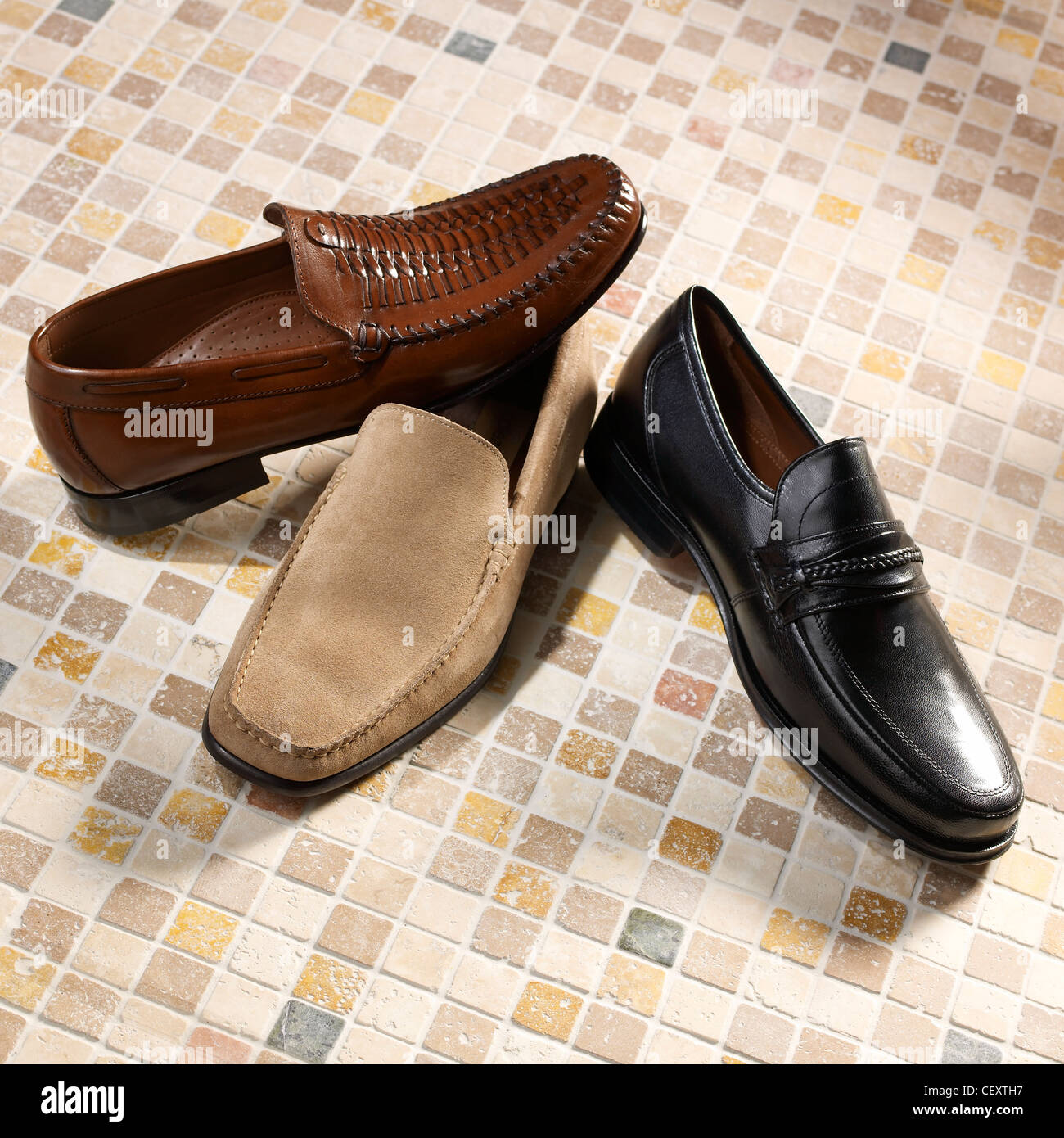 A still life shot of a three mens shoes on a mosiac floor - Stock Image