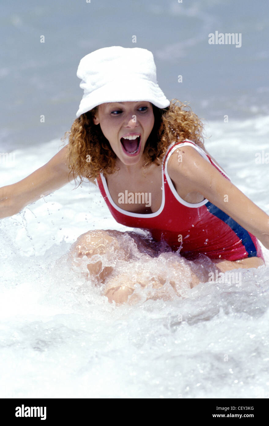 Female curly red hair wearing white sun hat and red swimming costume white  trim 39b62884a60