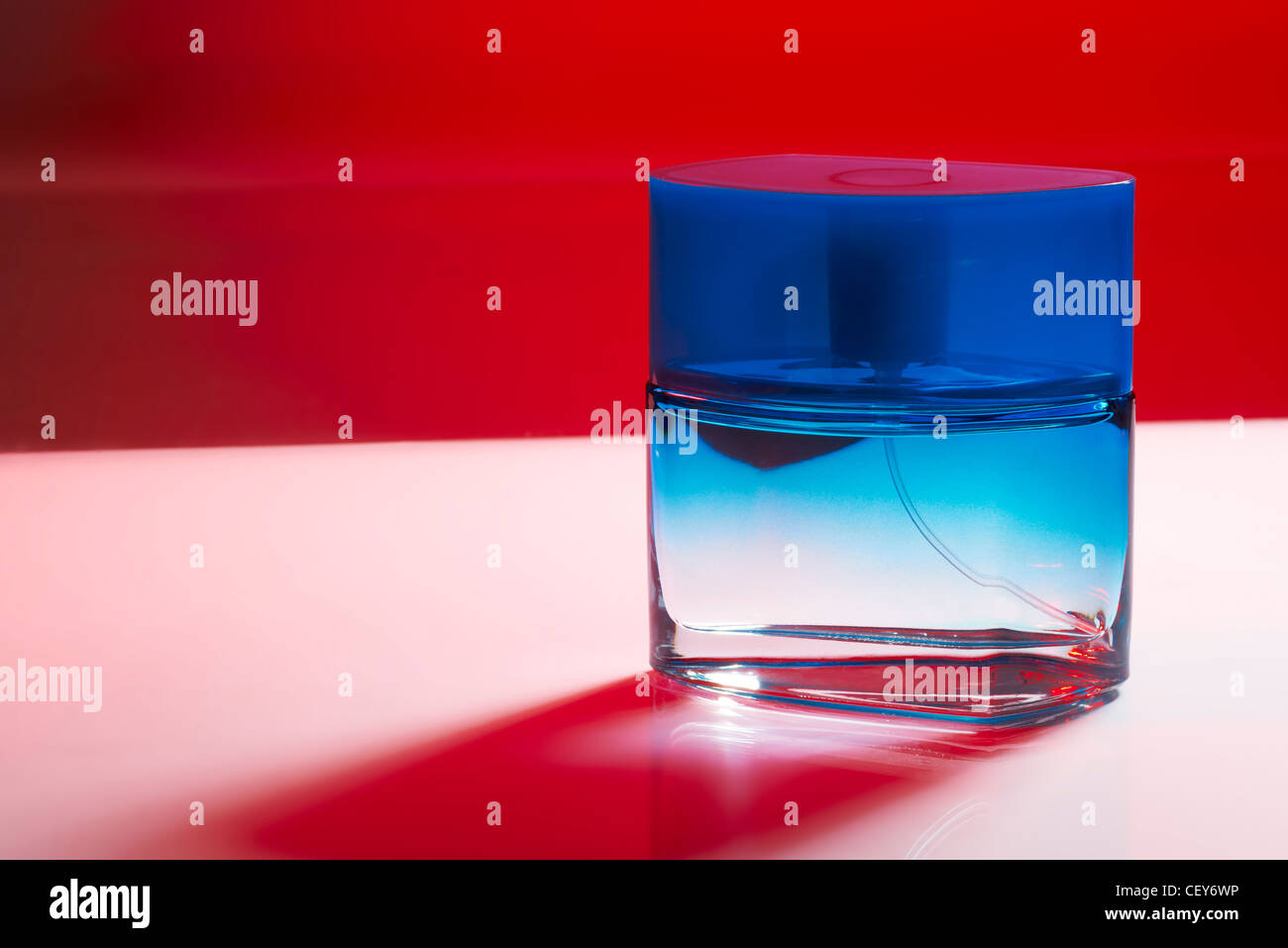 Blue perfume bottle on purple background with red shadow - Stock Image