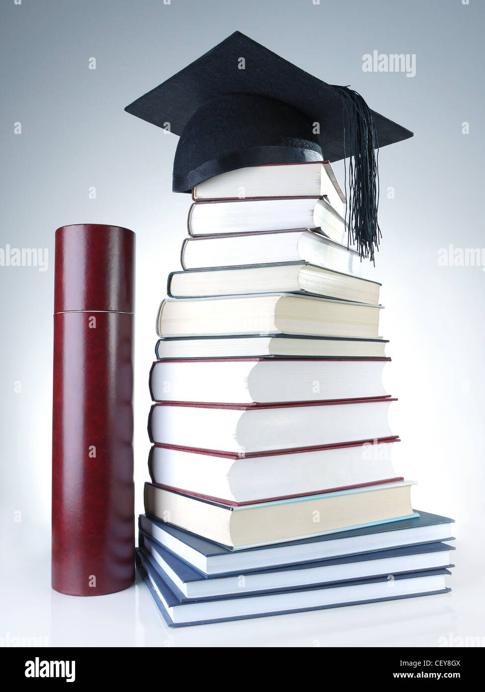 Black graduation cap on pile of books with diploma tube - Stock Image