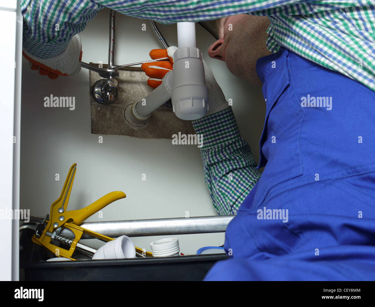 Plumber installing cold and hot water fixtures to bathroom washbasin - Stock Image