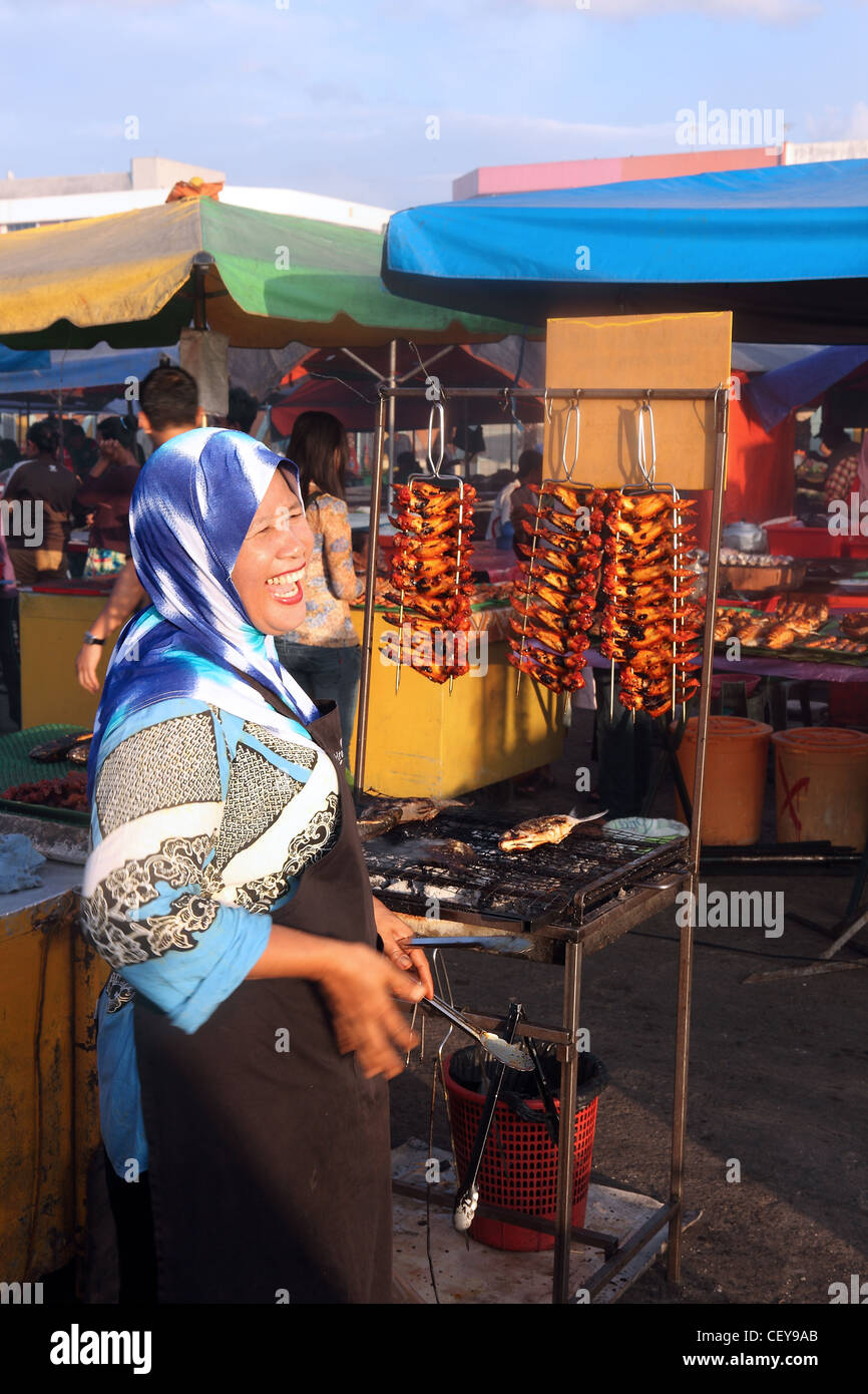 Muslim woman selling grilled chicken kebabs at the waterfront market. Kota Kinabalu, Sabah, Borneo, Malaysia, South - Stock Image