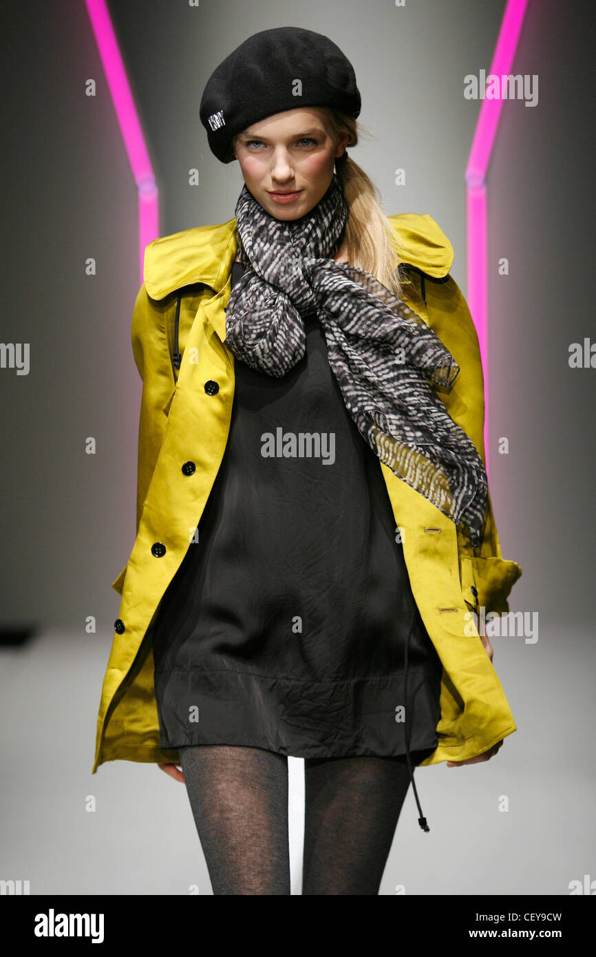DKNY New York Ready to Wear Autumn Winter Model wearing black tunic mini dress tie string toggle hem, light mustard - Stock Image
