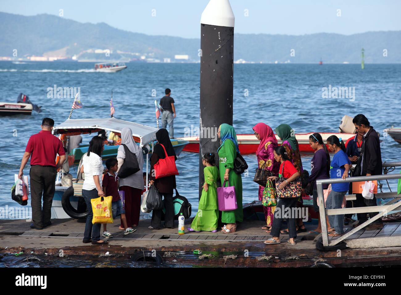 Passengers boarding water taxi on the waterfront. Kota Kinabalu, Sabah, Borneo, Malaysia, South-East Asia, Asia - Stock Image