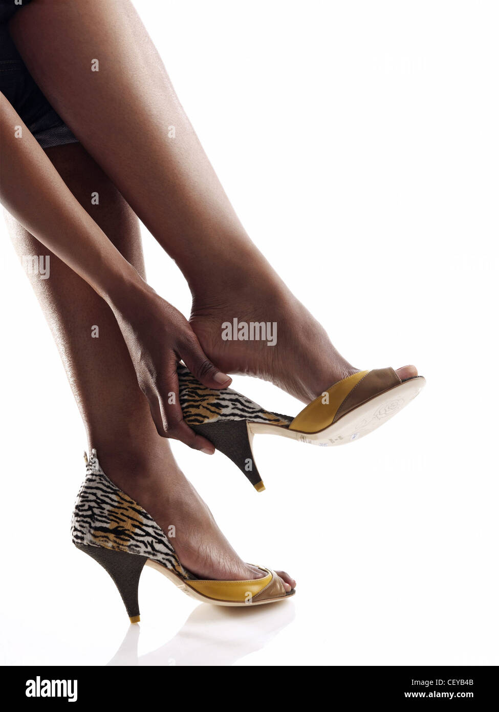 Female wearing yellow leopard print high heeled shoes taking shoe off - Stock Image