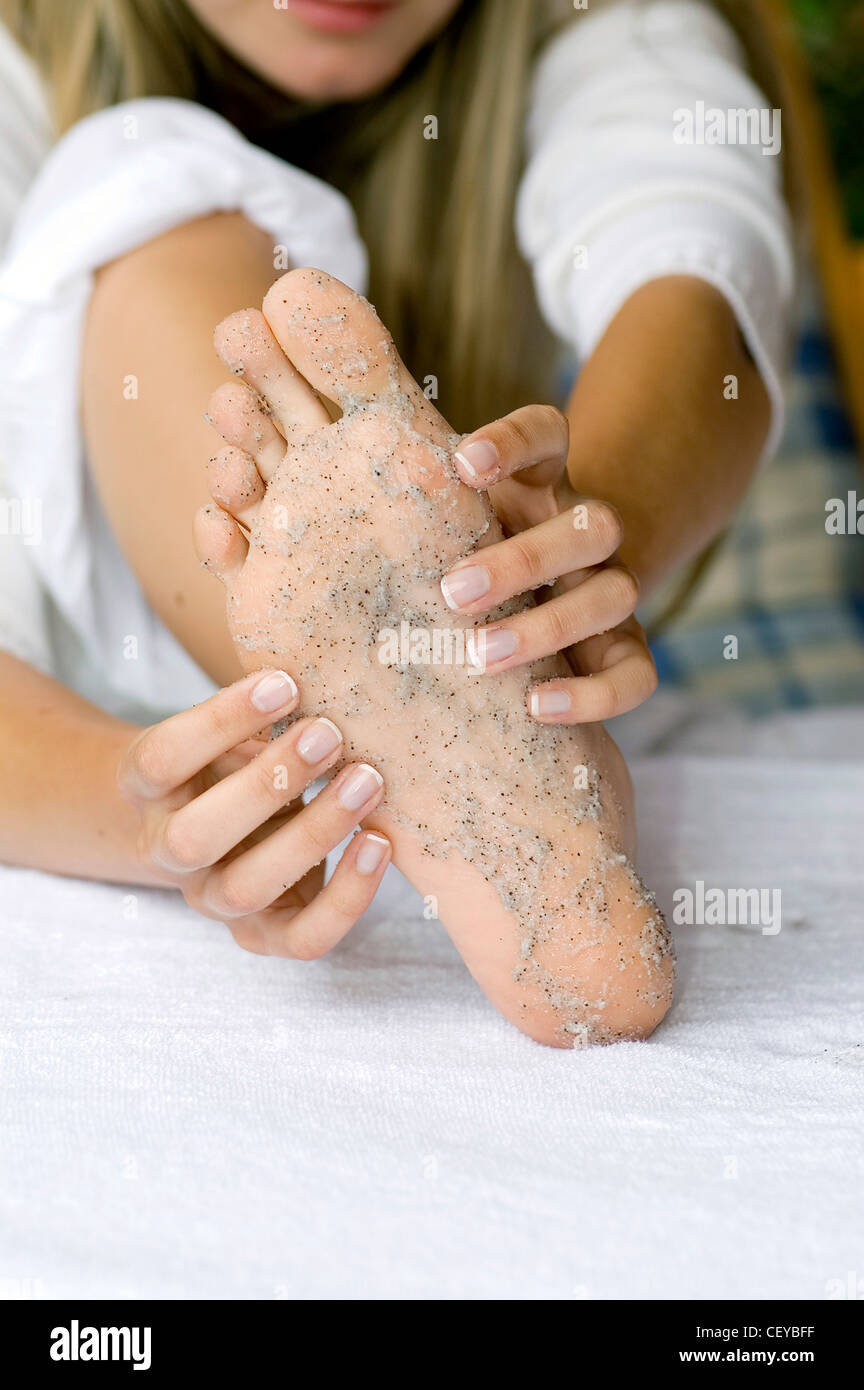 Female massaging grey foot scrub on sole of foot - Stock Image