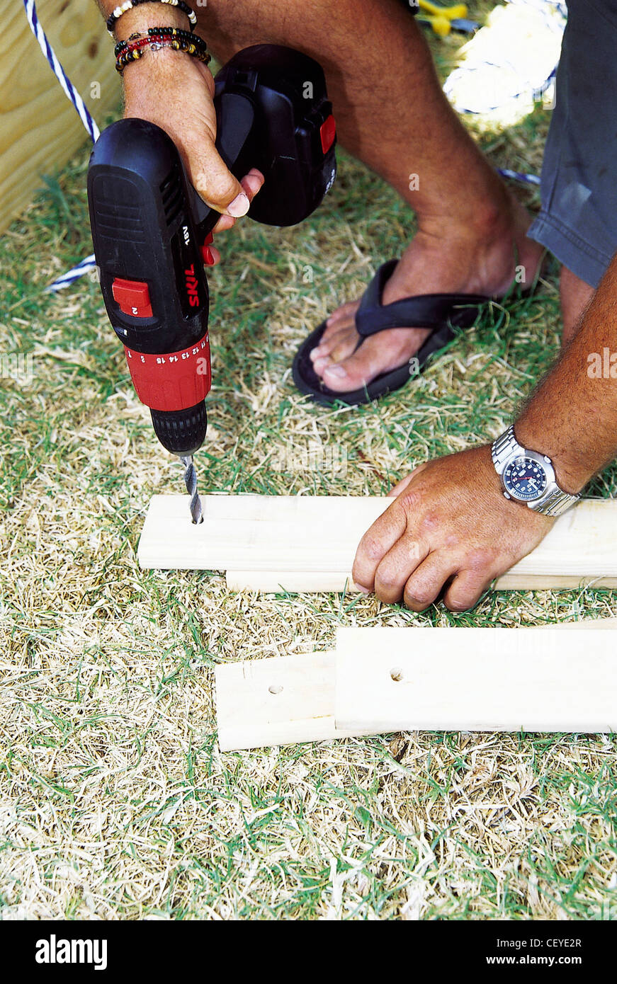 FORBuild a Tree House Step Male drilling holes in planks of wood to