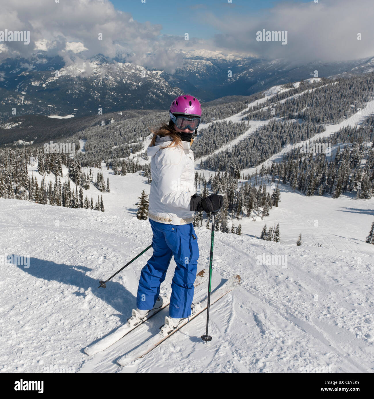 a skier on a ski trail with forests and mountains in the background; whistler british columbia canada - Stock Image