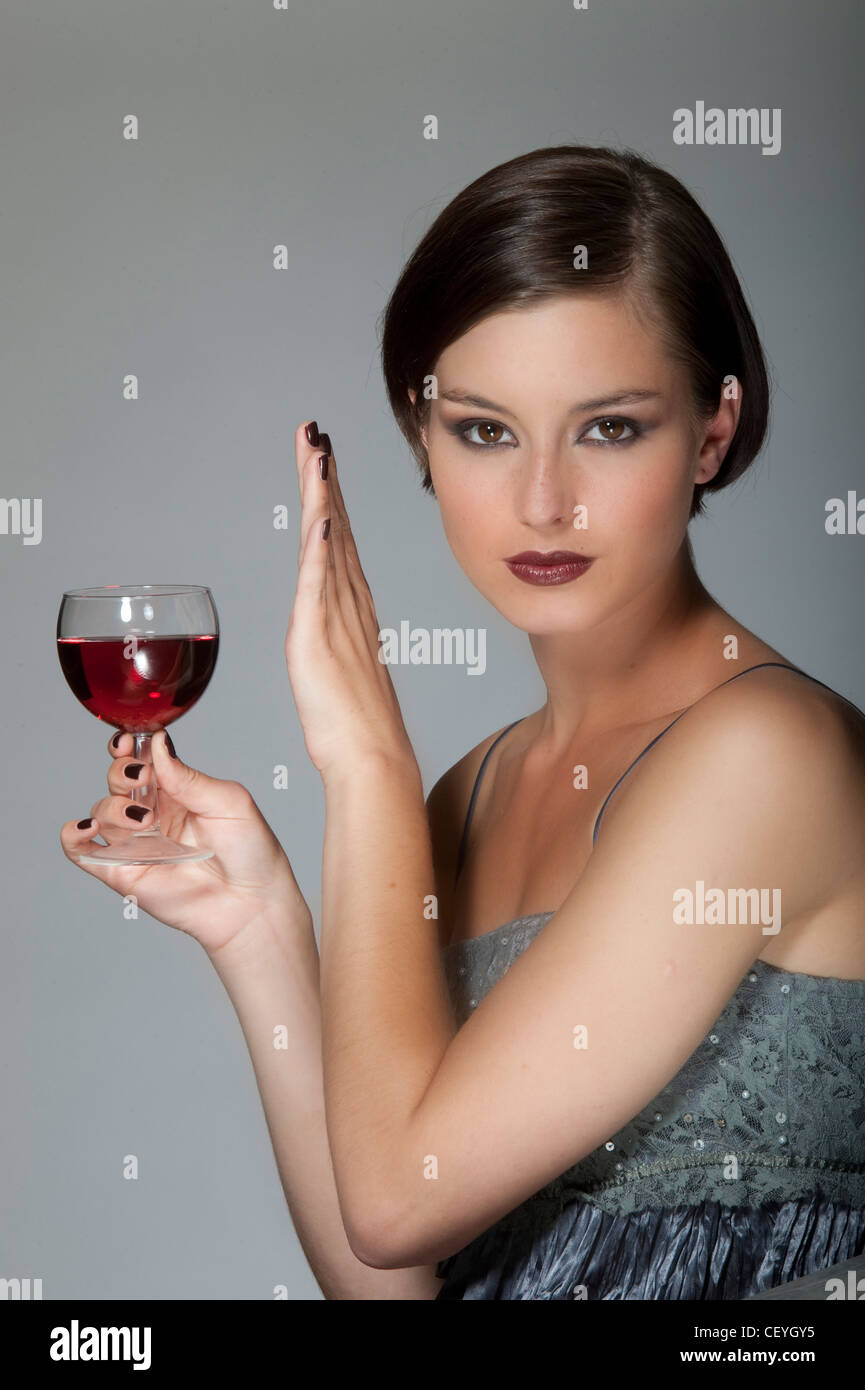 Female short brunette hair, wearing evening make up and silver dress, refusing a glass of red wine in one hand, unsmiling,