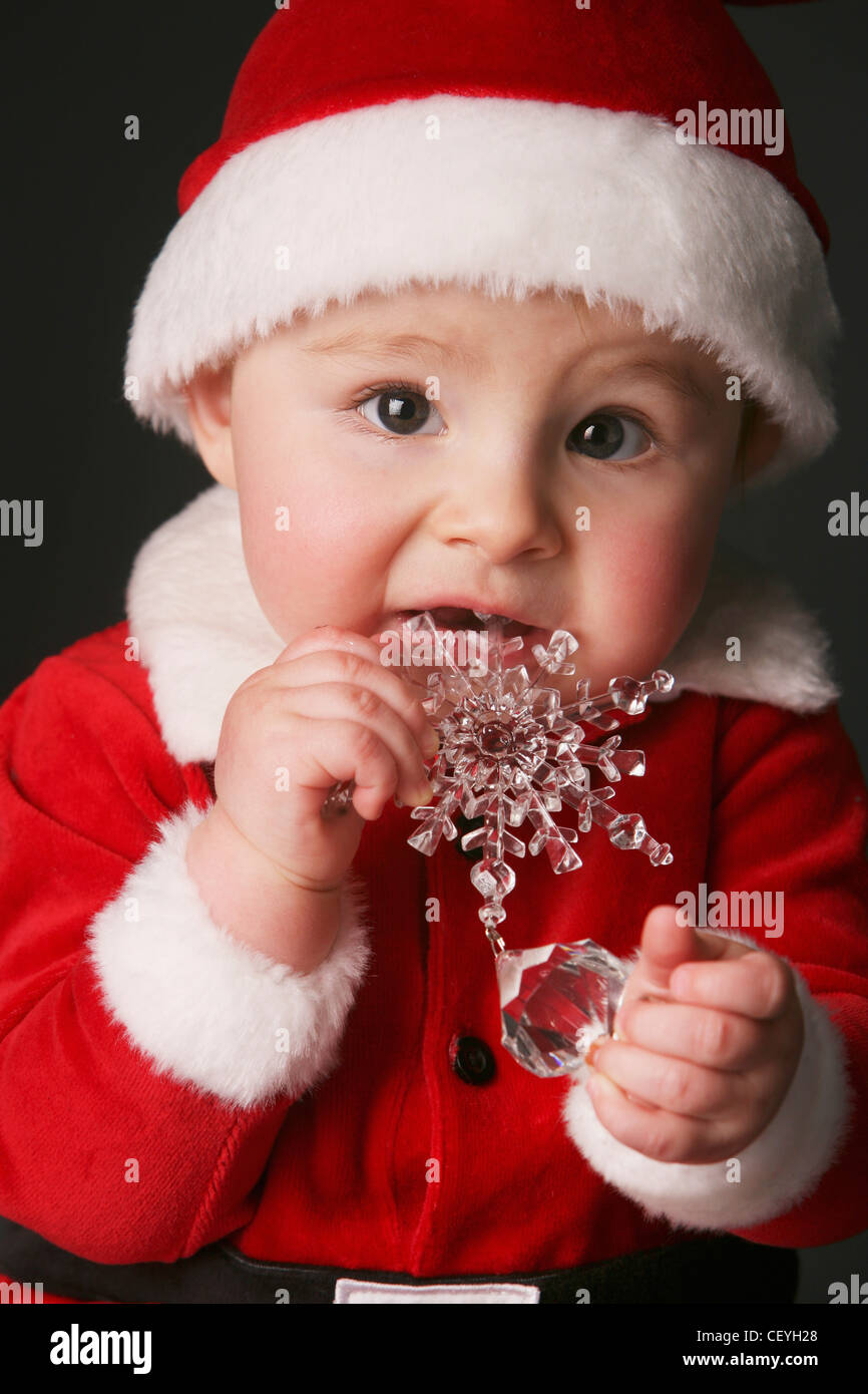 baby in a santa claus outfit chewing on an ornament; edmonton alberta canada - Stock Image