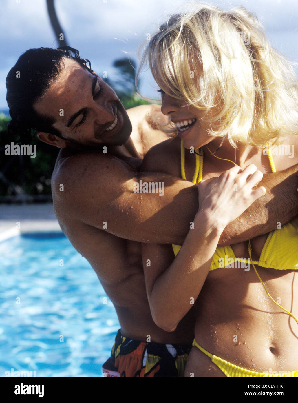 female blonde hair, wearing yellow bikini wrestling male wet