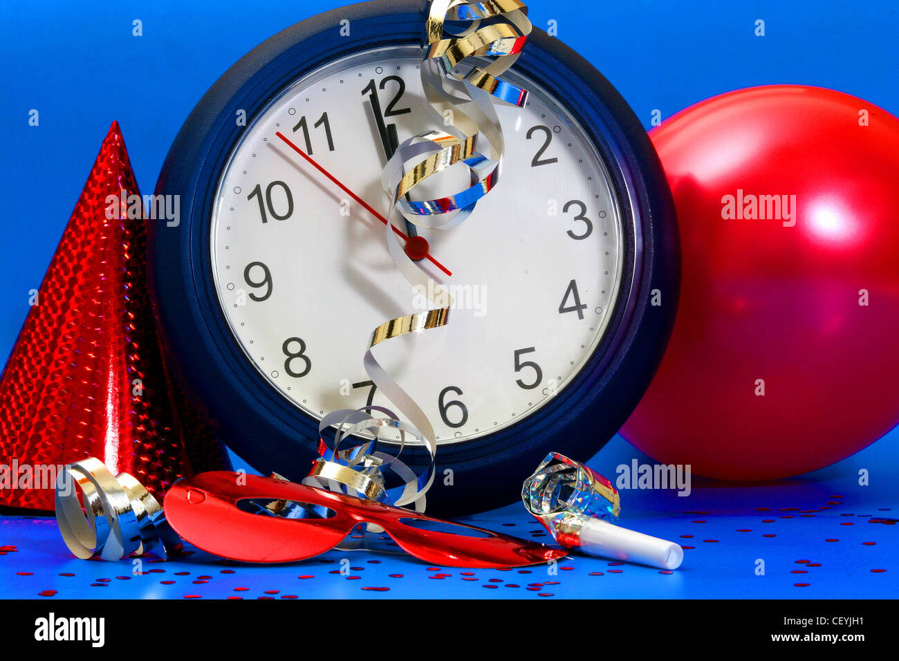 A clock stopped at seconds to midnight, a red metallic party hat next to it, a red balloon, red mask, metallic gold - Stock Image