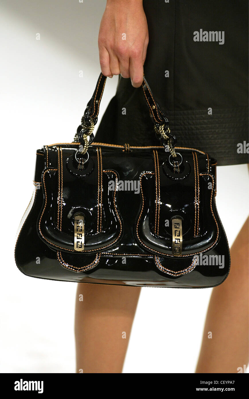 3f40ca4fadd0 Fendi Milan Ready to Wear S S Cropped hand of model carrying black patent  leather handbag -