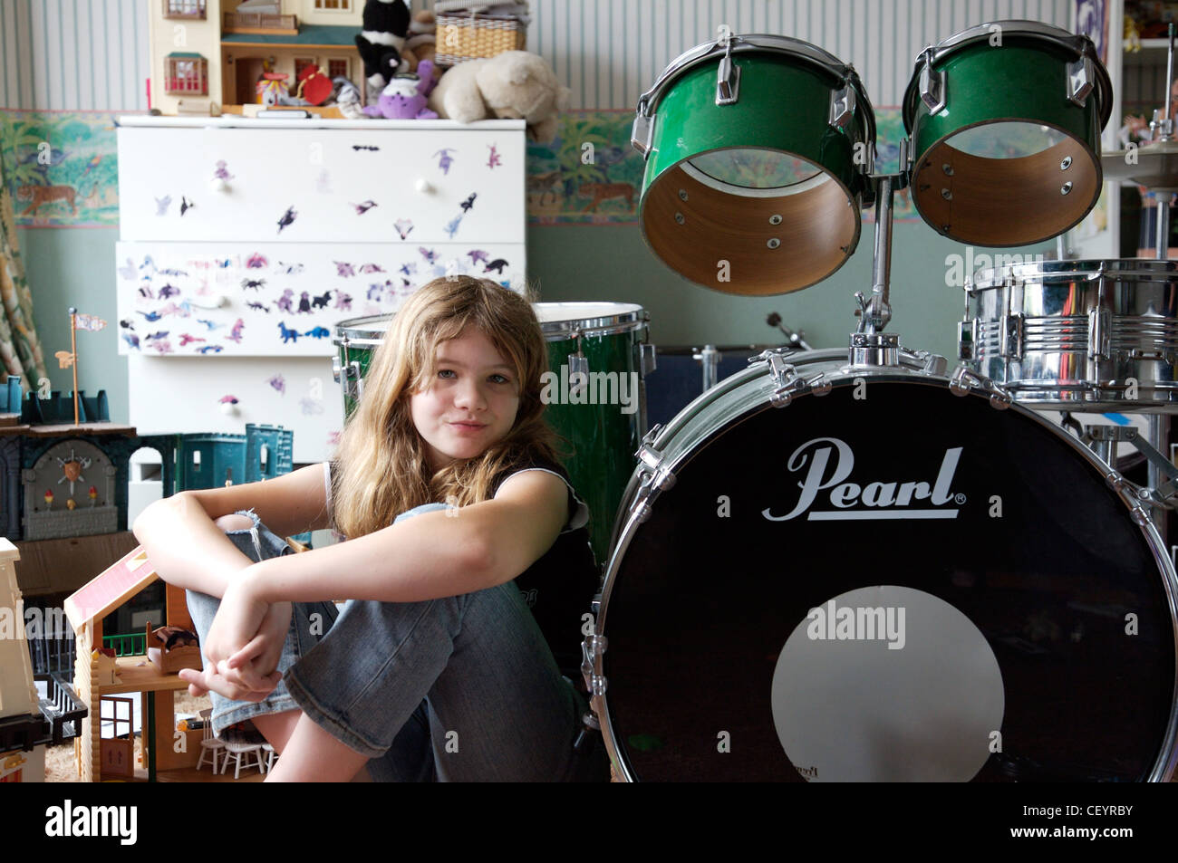 Female child, long blonde hair, black top, jeans, sitting on floby drum kit - Stock Image