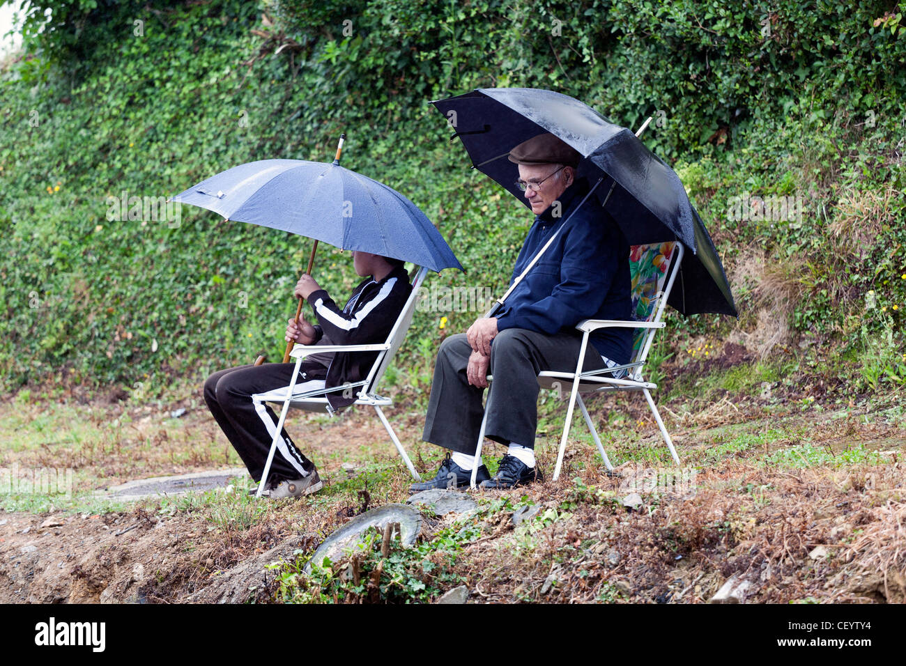 Two persons seated with umbrellas just relaxing under the rain Stock Photo