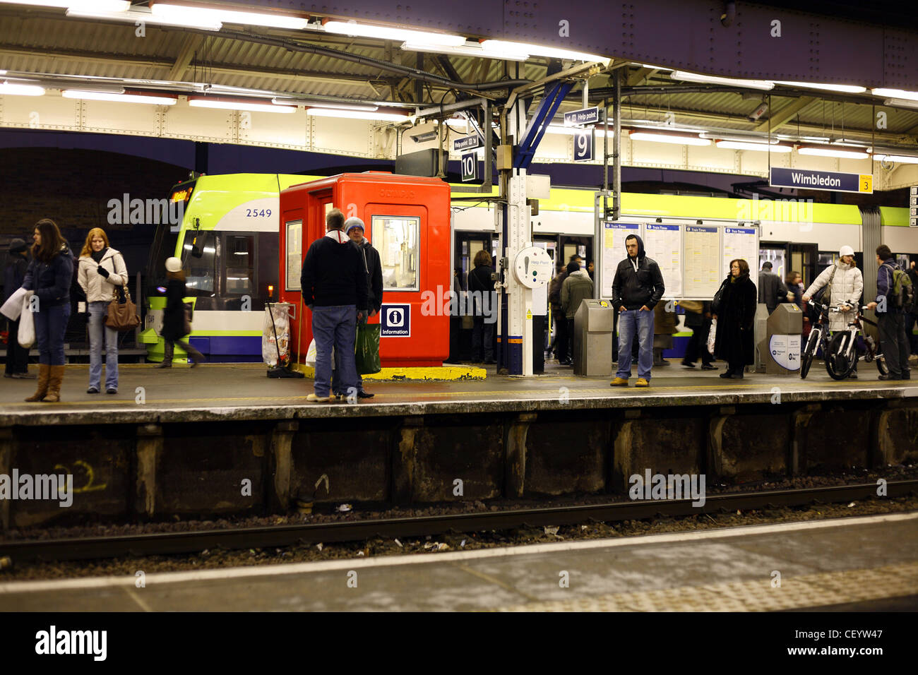 Passengers waiting for a train on a platform at Wimbledon train station in the evening. - Stock Image