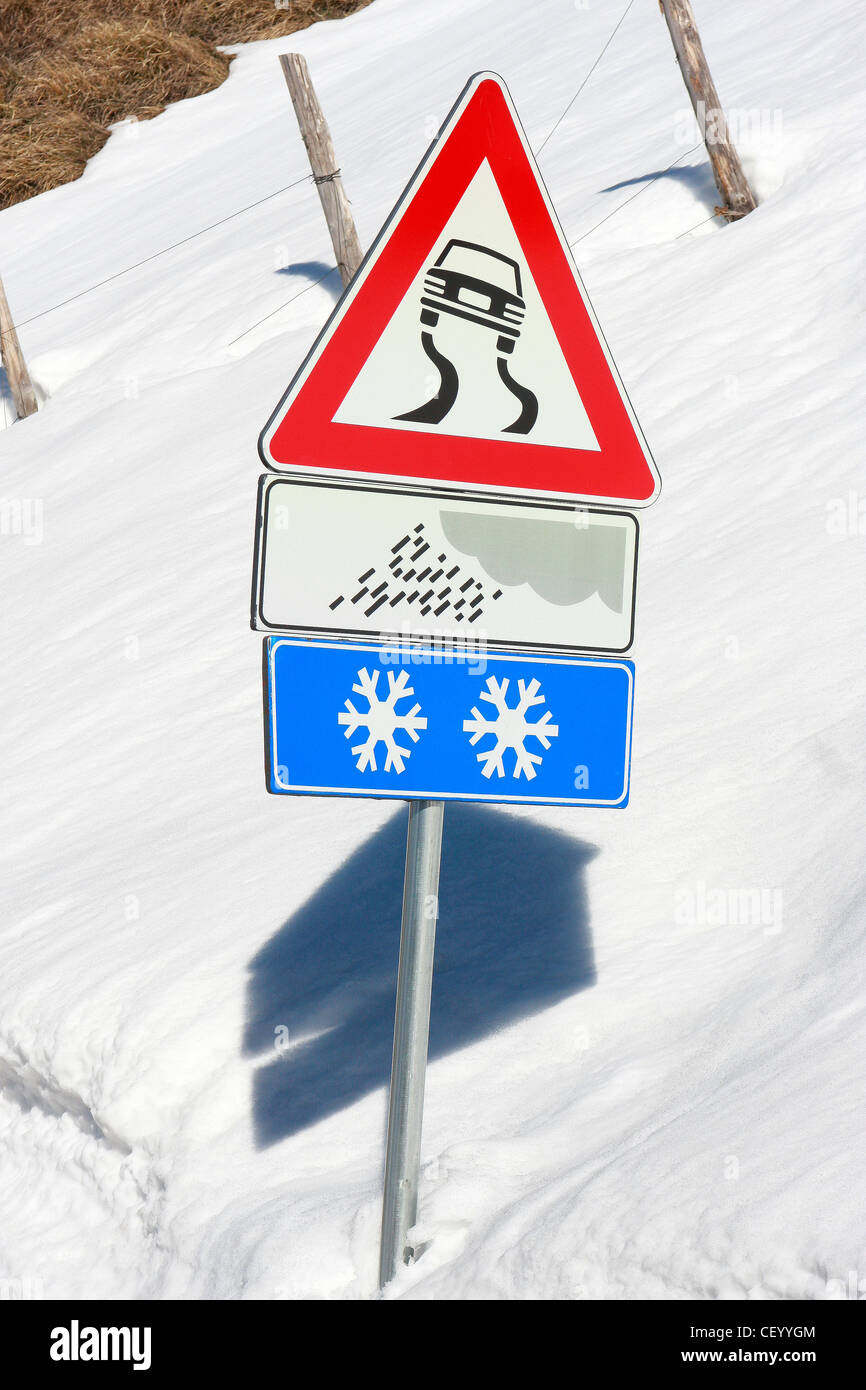 Winter Road signs warn of ice snow and slippery conditions in Italy - Stock Image