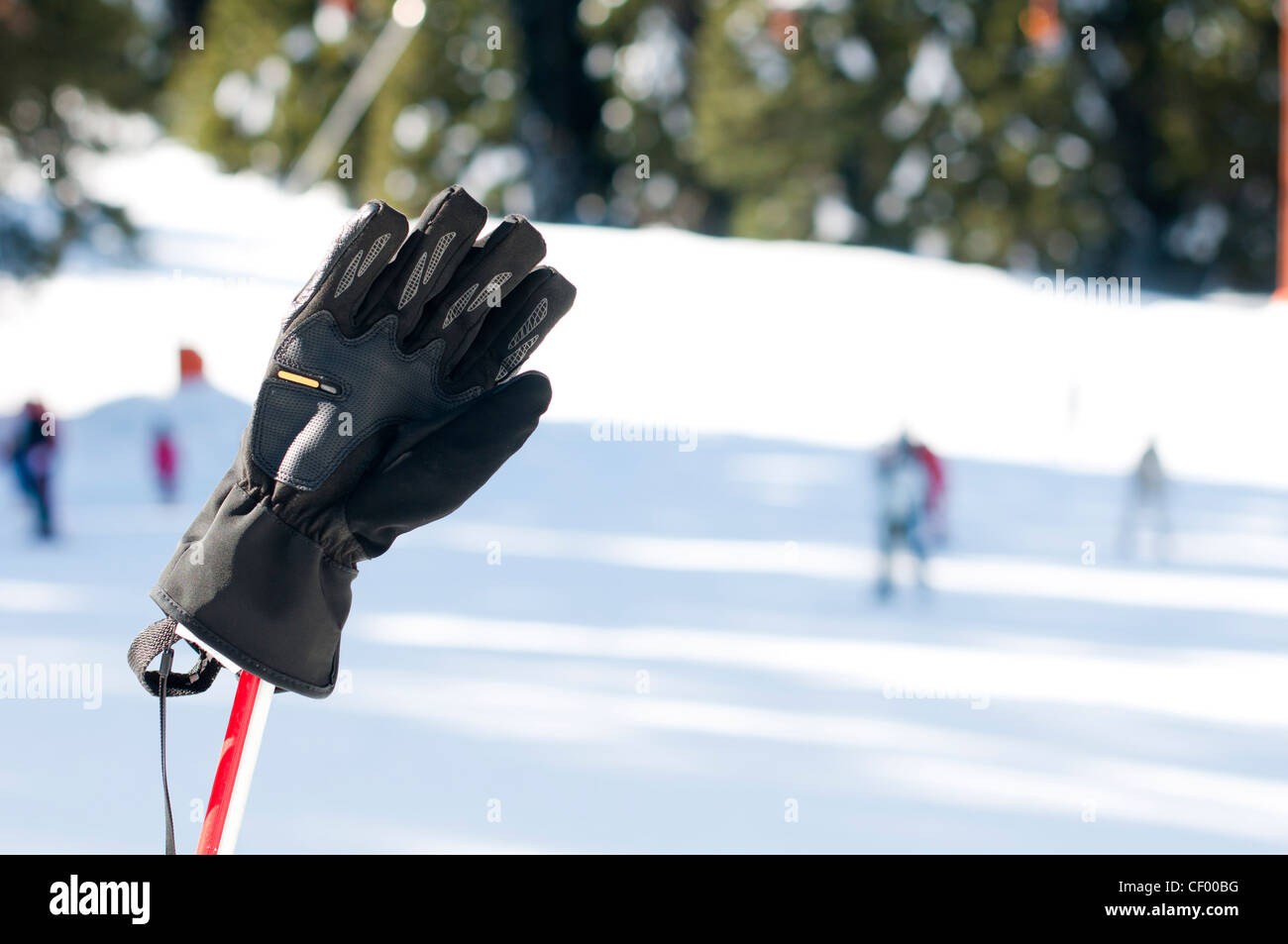Ski gloves and sticks. Winter tourists on the background. - Stock Image