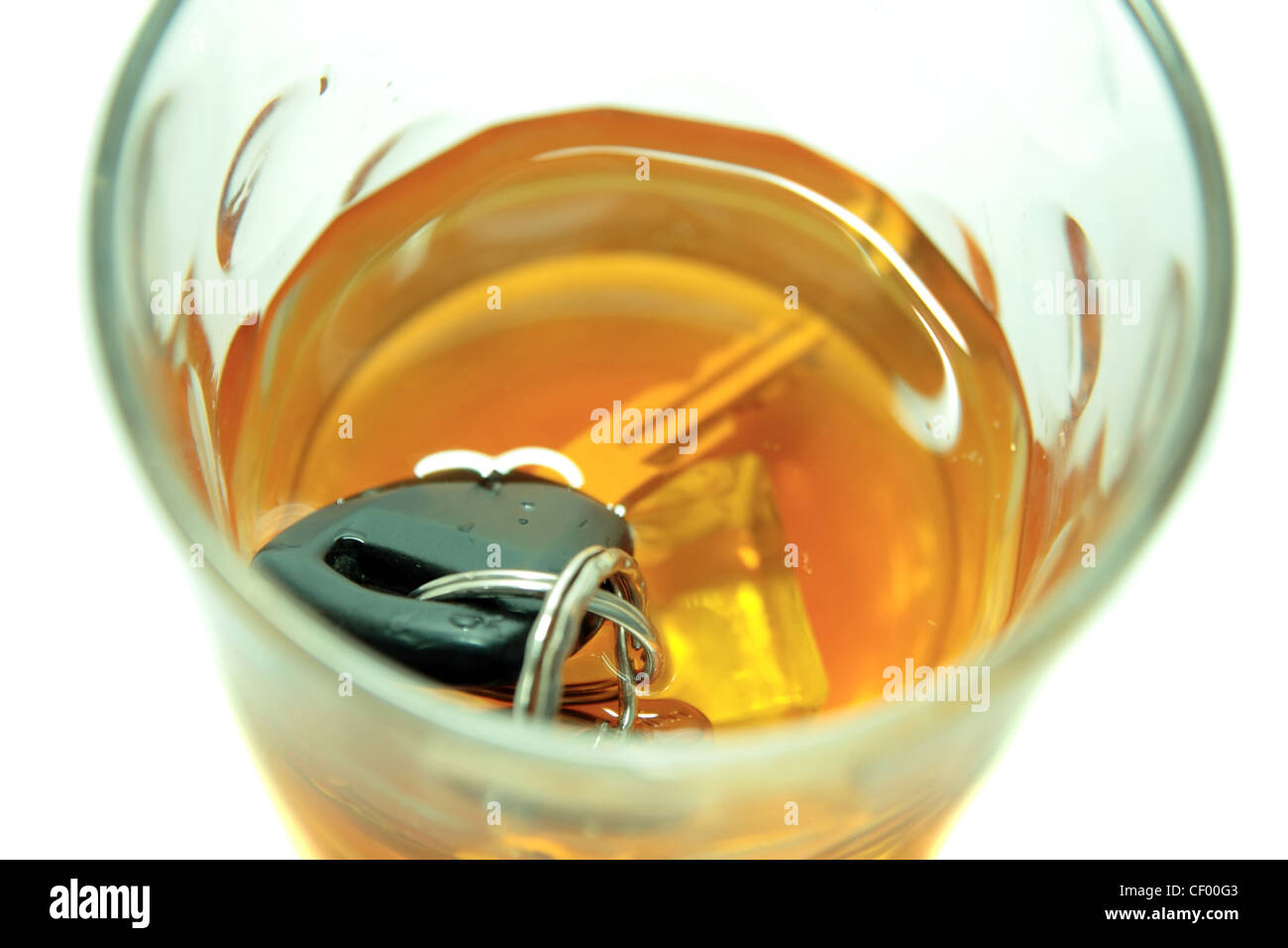 whiskey with keys inside glass on white background depicting drunk driving and addictions can kill - Stock Image