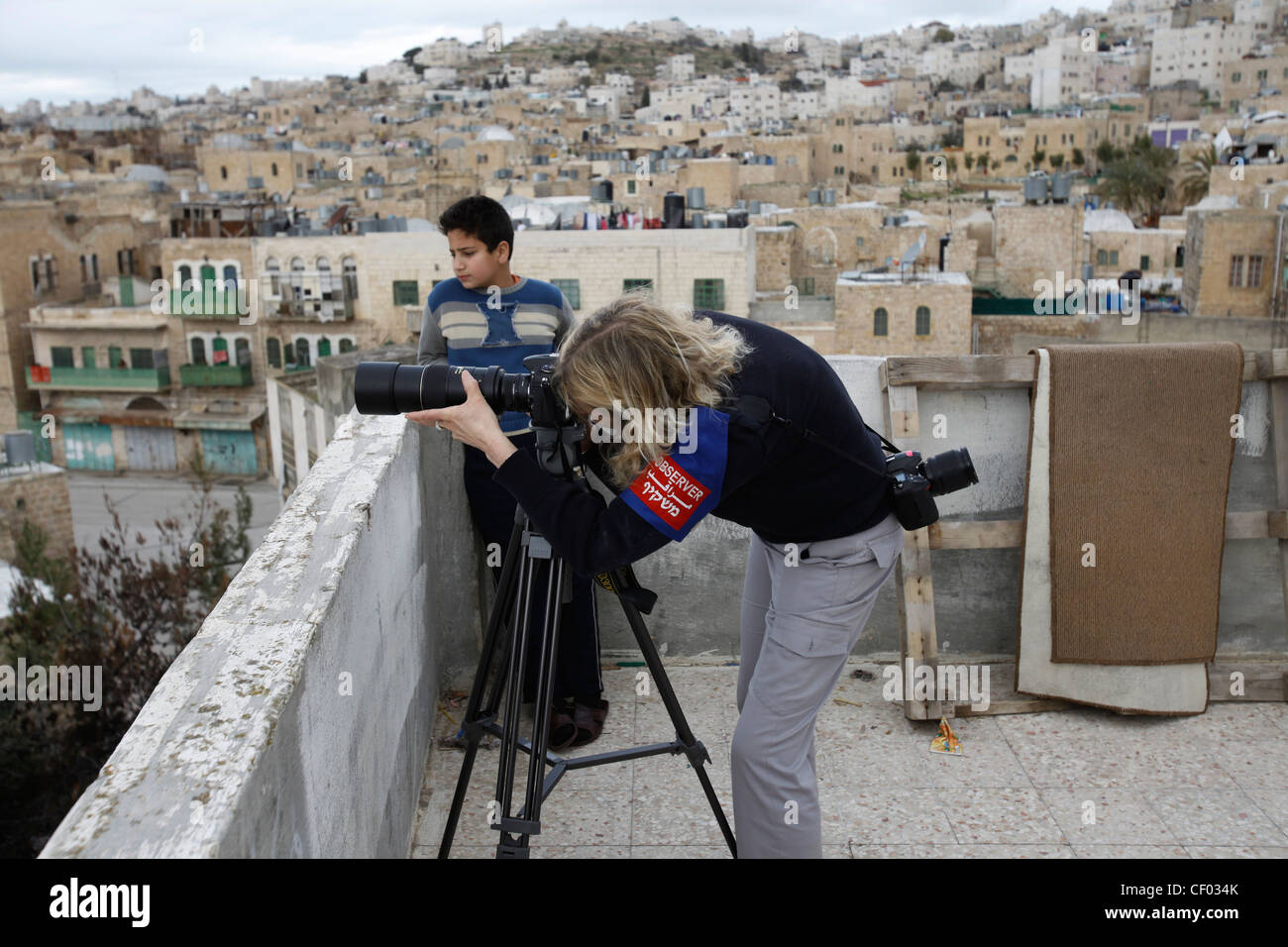 A TIPH (Temporary International Presence in Hebron) civilian observer from Norway photographing Israeli troops from - Stock Image